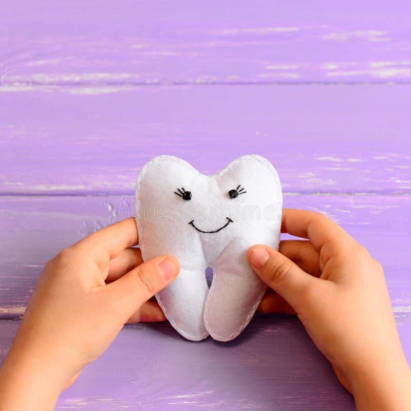 Il piccolo bambino ha fatto un giocattolo del fatato di dente del feltro Il bambino tiene un giocattolo del fatato di dente del f fotografie stock