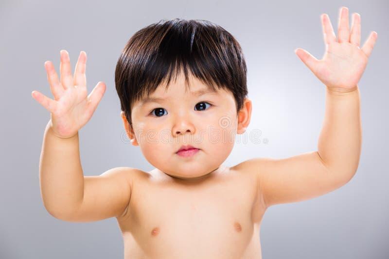 Il piccolo bambino ha sollevato la mano due immagini stock