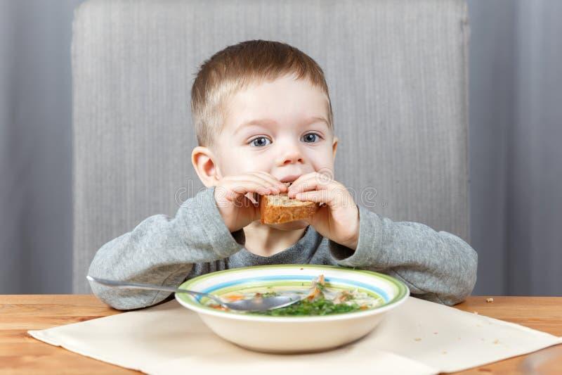 Il piccolo bambino morde fuori il pezzo di pane alla cena fotografie stock