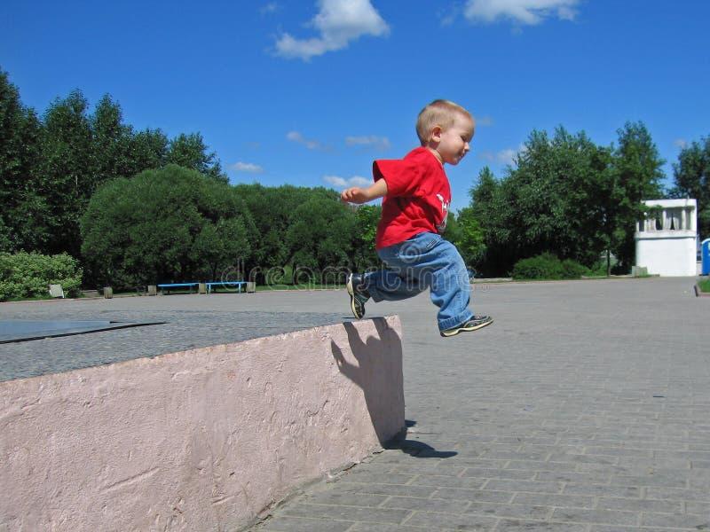 Il piccolo bambino salta lungamente immagine stock libera da diritti