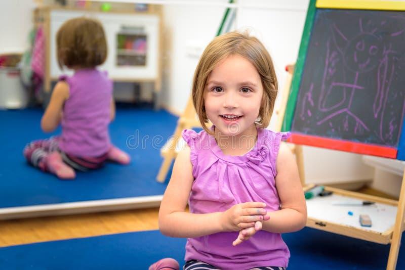 Il piccolo bambino sta disegnando con il gesso di colore sul bordo di gesso fotografia stock libera da diritti