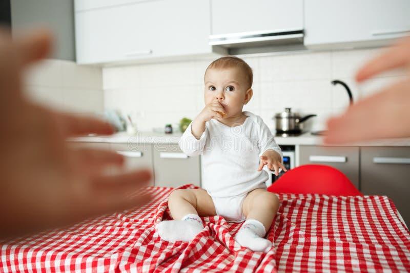 Il piccolo bambino sveglio con grande marrone osserva mangiando il porridge con le mani e considerando la mamma con l'espressione immagini stock libere da diritti