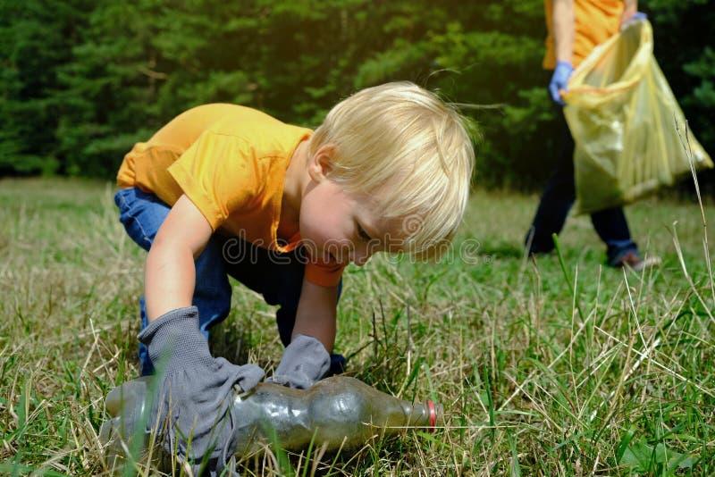Il piccolo bambino sveglio e suo il padre che raccolgono l'immondizia e la plastica imbottiglia il parco Volontari che prendono l fotografia stock