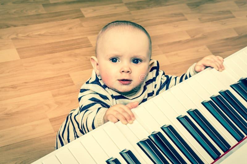 Il piccolo bambino sveglio gioca il piano - retro stile immagini stock libere da diritti