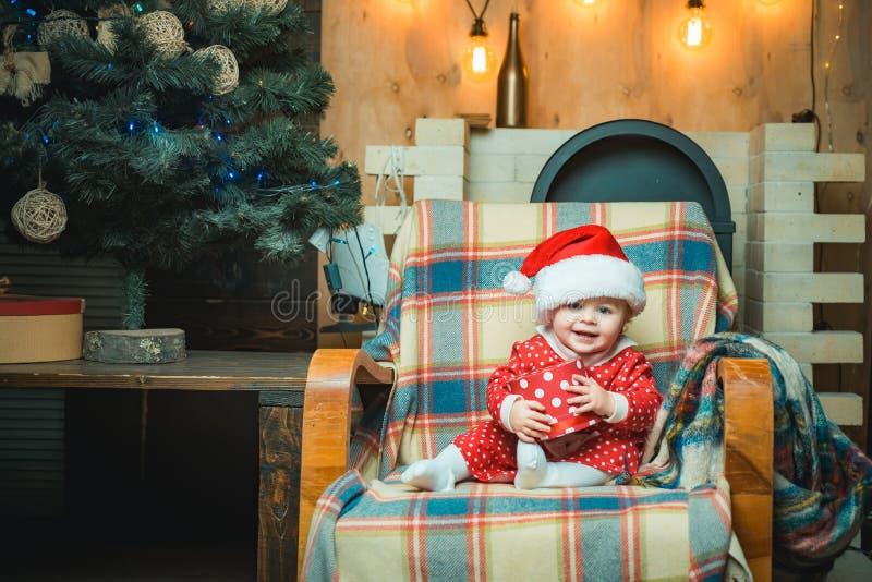 Il piccolo bambino sveglio sta decorando l'albero di Natale all'interno Concetto di vacanza invernale di Natale Bambino felice co immagini stock libere da diritti