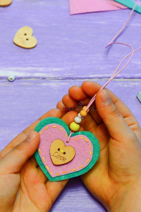 Il piccolo bambino tiene una collana del pendente del cuore del feltro in sue mani Il bambino ha fatto una collana del pendente d immagini stock