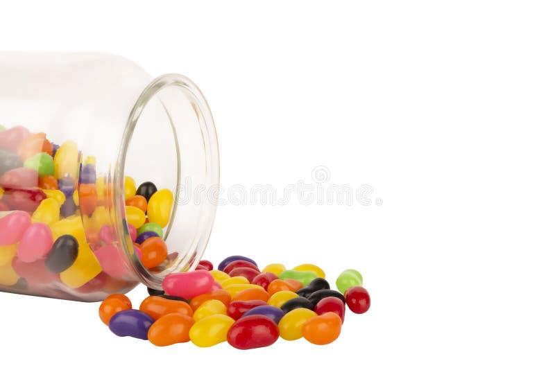 Il piccolo barattolo di vetro con i fagioli di gelatina colorati ha sparso isolato su fondo bianco fotografie stock