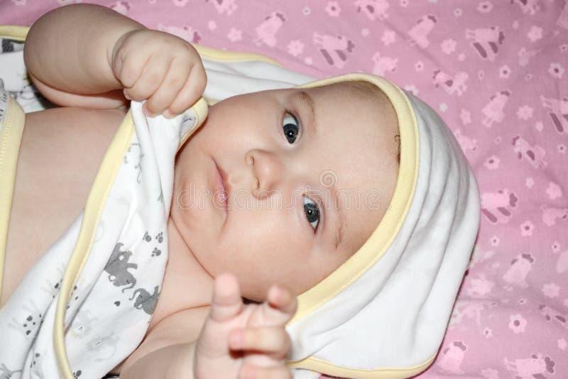 Il piccolo bello bambino in asciugamano si trova sul letto fotografia stock libera da diritti