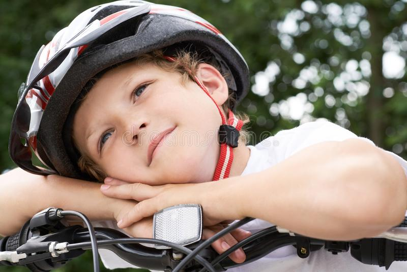 Il piccolo ciclista caucasico del ragazzo in casco protettivo ha messo la sua testa sul manubrio della bici che posa per la macch fotografie stock