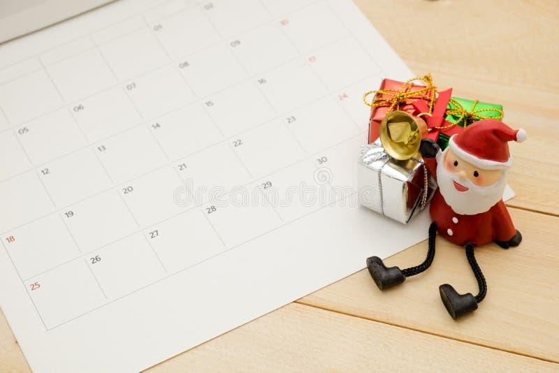 Il piccolo contenitore di regalo tre e Claus satan hanno messo sopra il fondo di legno fotografia stock libera da diritti