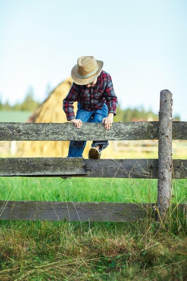 Il piccolo cowboy scavalca il recinto di legno, all'aperto fotografie stock libere da diritti