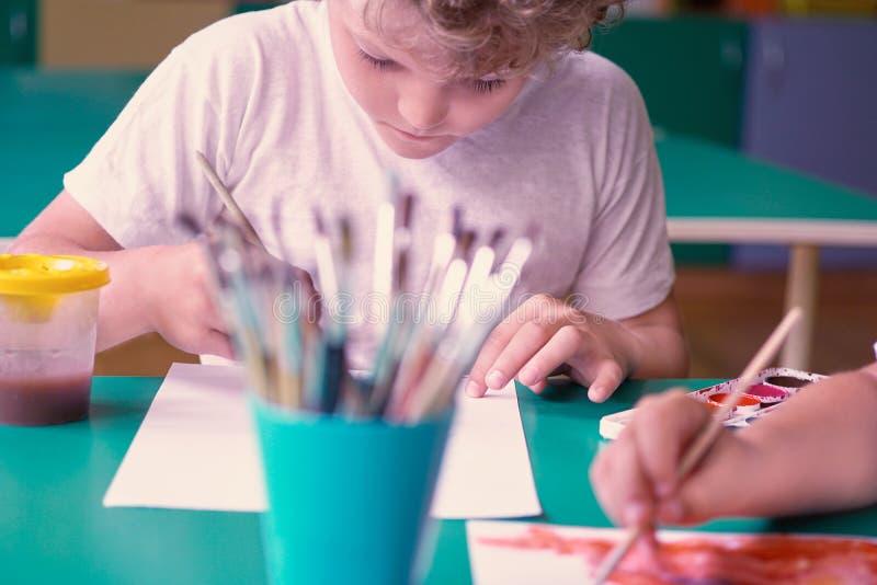 Il piccolo disegno caucasico riccio del ragazzo fiorisce con gli acquerelli variopinti nell'asilo Concetto di formazione immagine stock