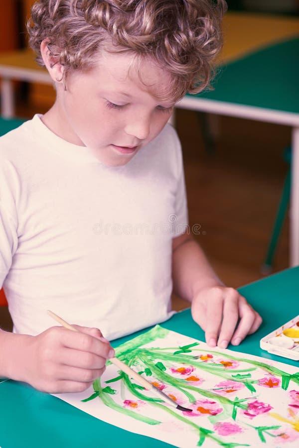 Il piccolo disegno caucasico riccio del ragazzo fiorisce con gli acquerelli variopinti nell'asilo Scuola, concetto di istruzione immagini stock