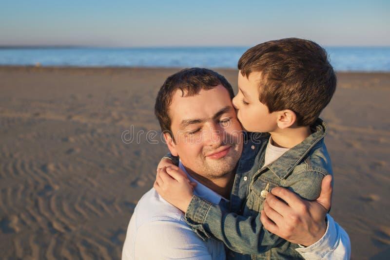 Il piccolo figlio bacia suo padre su una spiaggia fotografia stock libera da diritti
