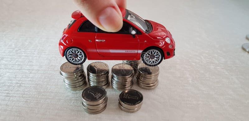 Il piccolo giocattolo rosso di Fiat 500 in suo consegna il mucchio delle monete israeliane dello shekel ha sistemato uno sulle al fotografia stock libera da diritti
