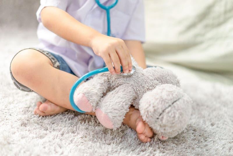 Il piccolo gioco asiatico felice del ragazzo finge di essere un medico bambino asiatico esaminarlo orsacchiotto con lo stetoscopi immagine stock libera da diritti