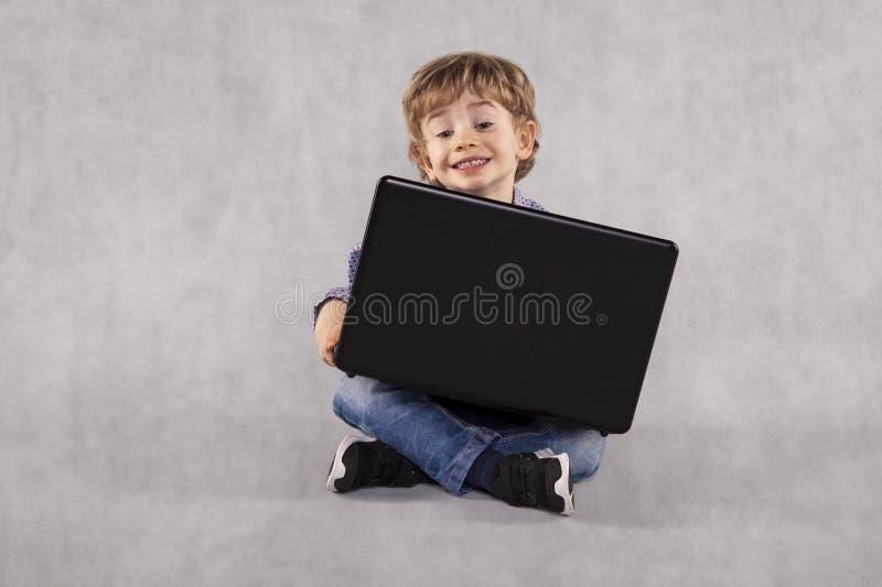 Il piccolo imprenditore utilizza un computer portatile, imparante da un'età giovane immagine stock libera da diritti