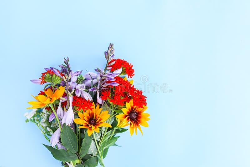 Il piccolo mazzo del giardino fiorisce su fondo blu-chiaro Campanula, lychnis e rudbeckia o margherita gialla decorativo porpora  fotografie stock libere da diritti