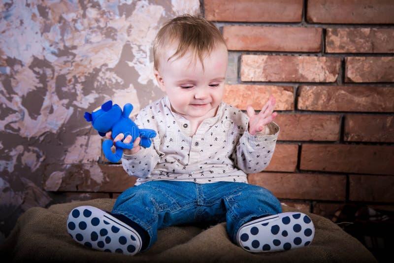 Il piccolo neonato è confuso e non capisce che cosa sta accadendo qui Sta sedendosi su un barilotto del ferro Bambino infantile s fotografia stock