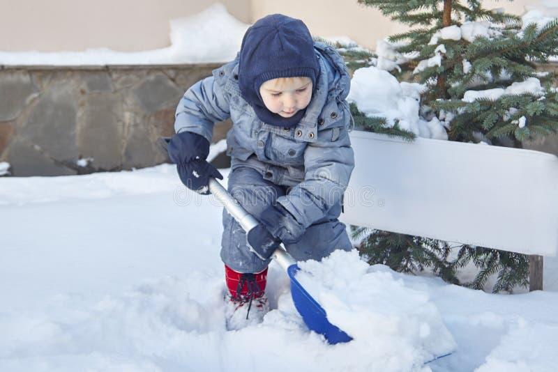 Il piccolo neonato caucasico sveglio spala la neve nell'iarda con l'abete su fondo Aria aperta di inverno, sorridendo, guance ros immagini stock