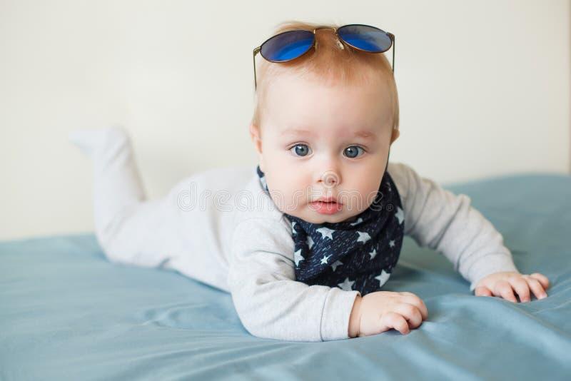 Il piccolo neonato divertente con i grandi occhi azzurri e gli occhiali da sole sul suo si dirigono fotografie stock