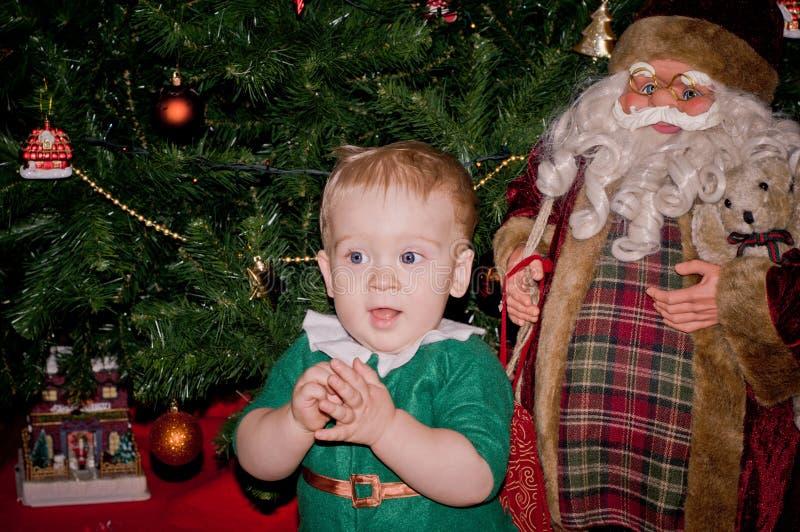 Il piccolo neonato si siede sotto l'albero di Natale decorato con Santa fotografia stock