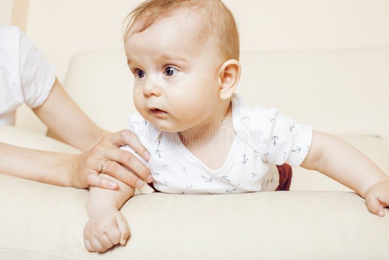 Il piccolo neonato sveglio che gioca sulla sedia, madre del bambino assicura la mano della tenuta, concetto della gente di stile  immagine stock