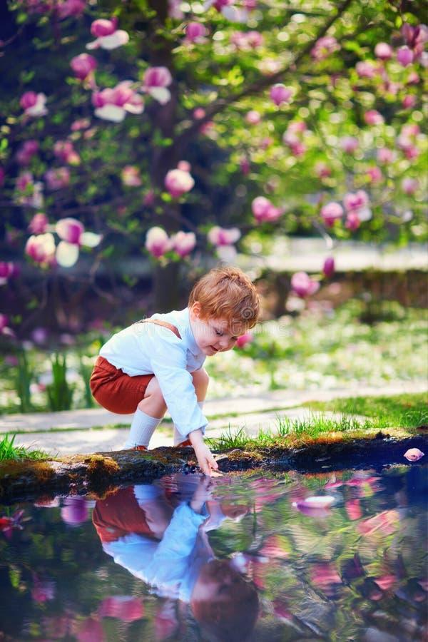 Il piccolo neonato sveglio mette la sua mano nell'acqua dello stagno nel giardino di primavera fotografia stock libera da diritti
