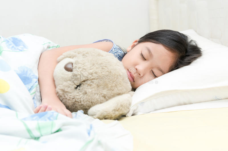 Il piccolo orsacchiotto asiatico sveglio di sonno e dell'abbraccio della ragazza riguarda il letto fotografia stock libera da diritti
