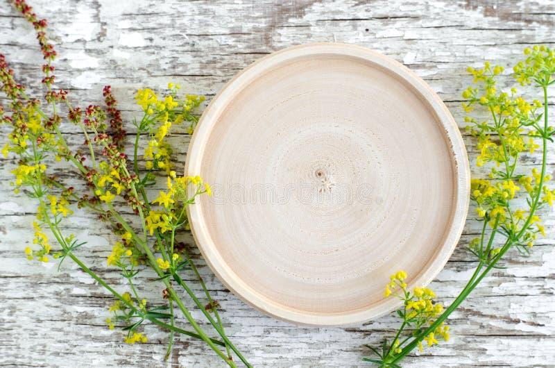 Il piccolo piatto di legno come posto per testo ed il piccolo campo fiorisce sui precedenti di legno miseri bianchi Erbario, medi immagine stock
