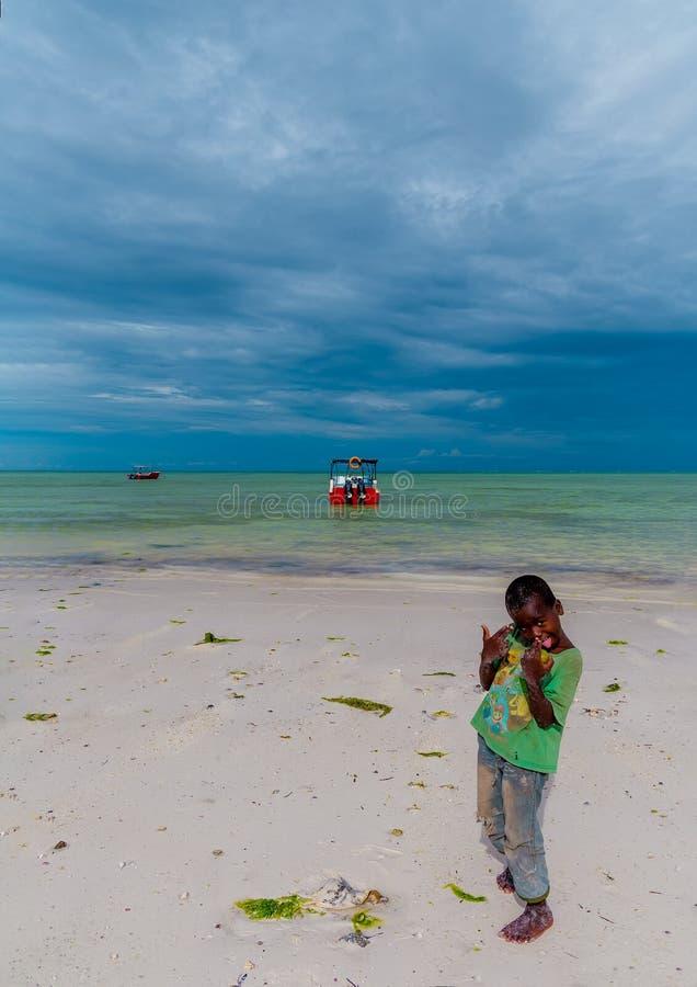 Il piccolo ragazzo africano sta vicino all'oceano nei precedenti di una barca fotografia stock