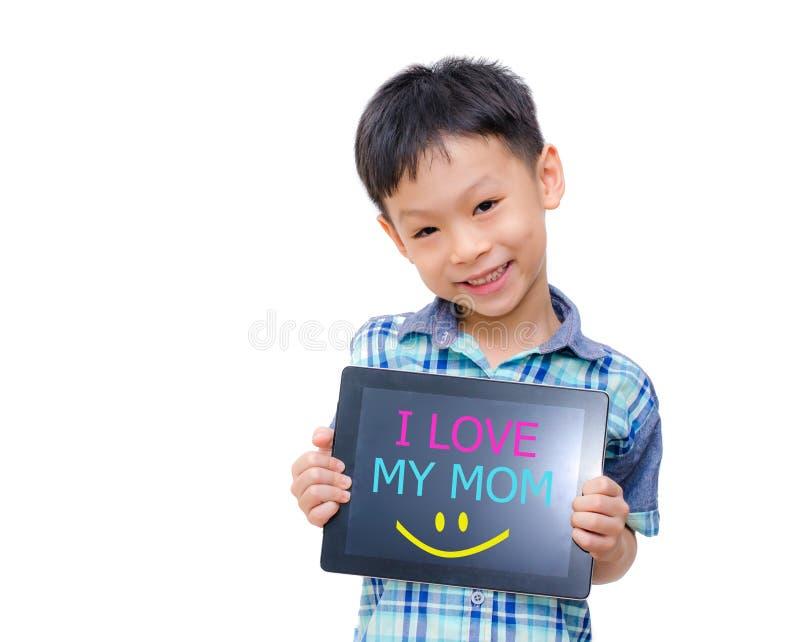 Il piccolo ragazzo asiatico sorride con il computer della compressa su fondo bianco fotografia stock