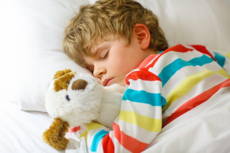Il piccolo ragazzo biondo del bambino in indumenti da letto variopinti copre il sonno immagini stock libere da diritti