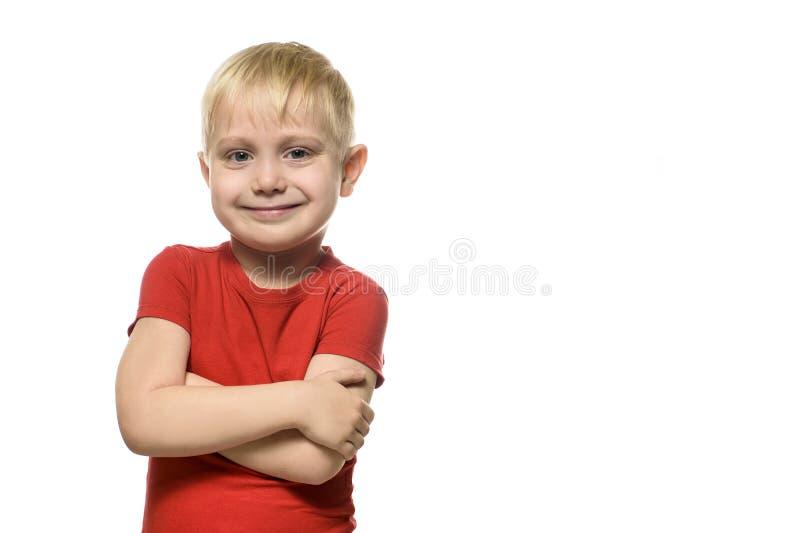 Il piccolo ragazzo biondo sorridente in una maglietta rossa sta con le armi piegate Isolato su fondo bianco fotografia stock