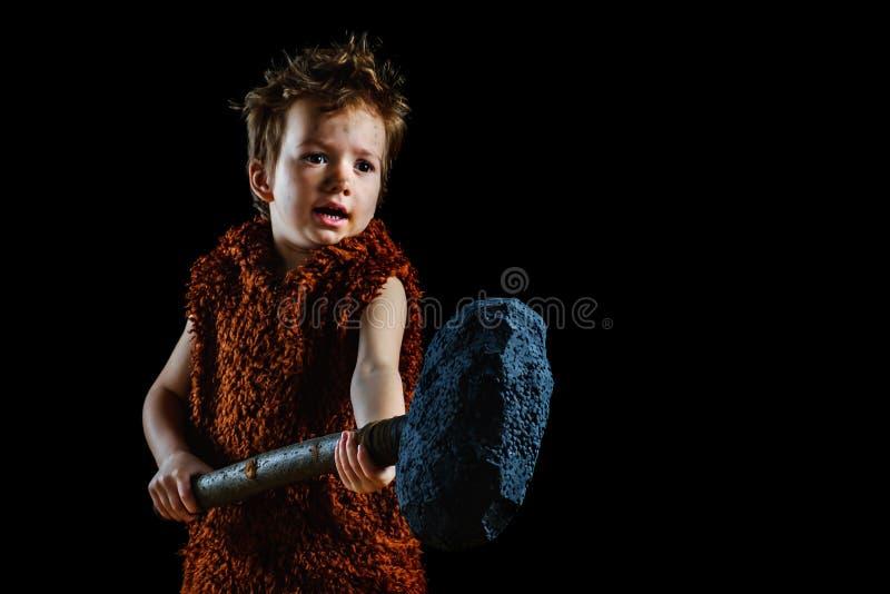 Il piccolo ragazzo divertente è un neanderthal o un'Ass.Comm.-Magnon Un cavernicolo antico con un'ascia enorme è isolato sul nero fotografia stock libera da diritti