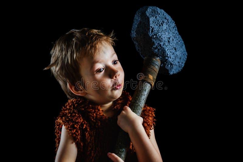 Il piccolo ragazzo divertente è un neanderthal o un'Ass.Comm.-Magnon Un cavernicolo antico con un'ascia enorme è isolato sul nero immagini stock
