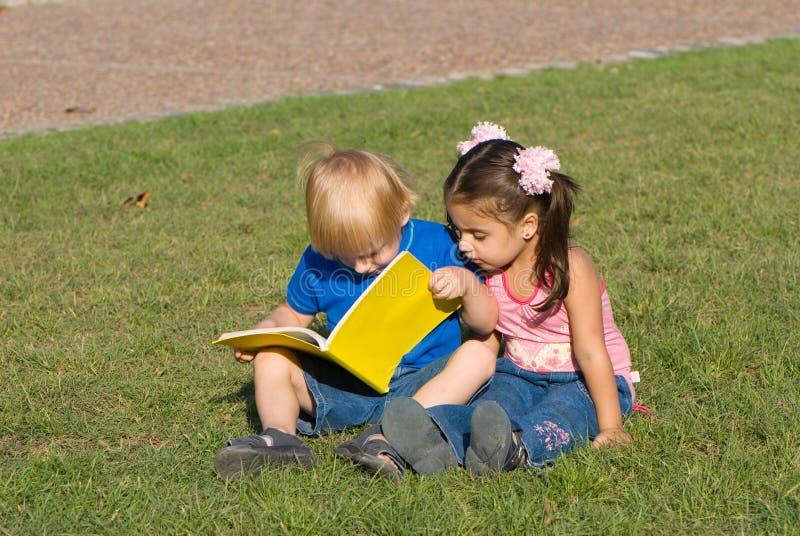 Il piccolo ragazzo e la ragazza su un glade in sosta hanno letto immagine stock libera da diritti