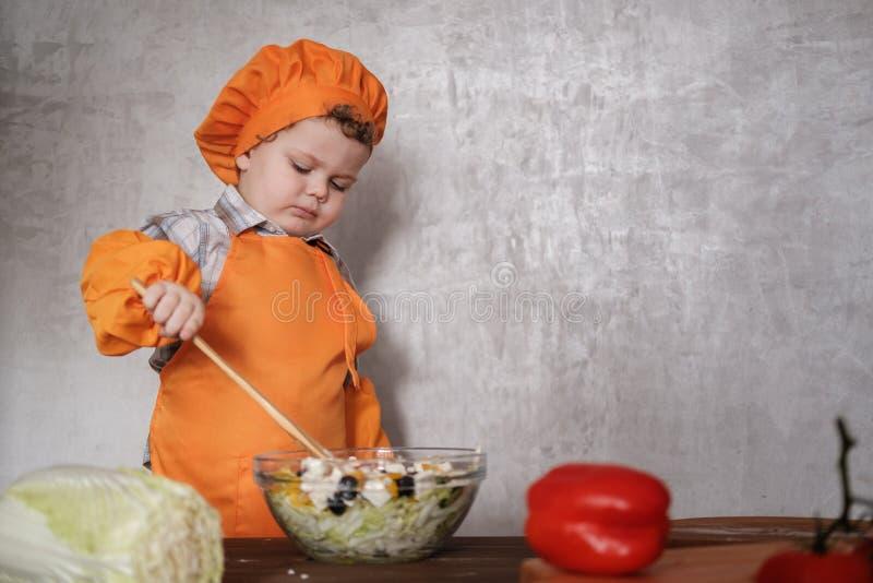 Il piccolo ragazzo europeo divertente vestito come un cuoco unico mescola un'insalata greca con un cucchiaio immagini stock libere da diritti