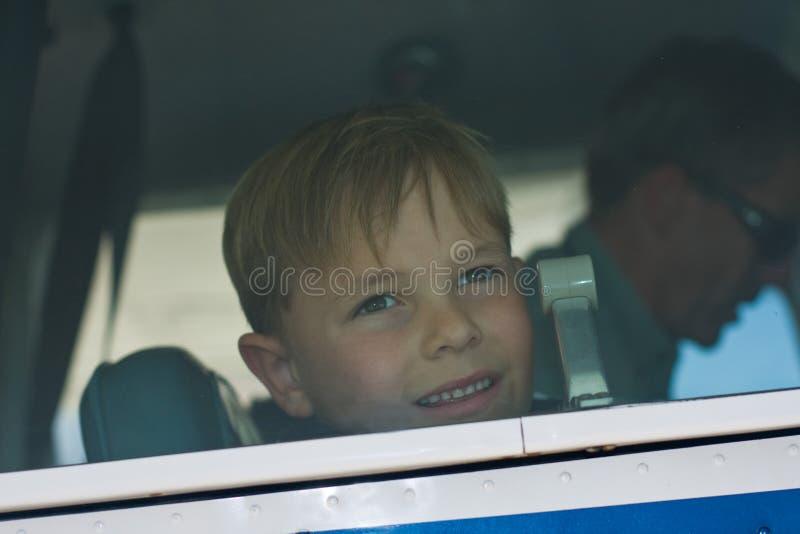Il piccolo ragazzo osserva fuori la finestra dell'aeroplano fotografia stock libera da diritti