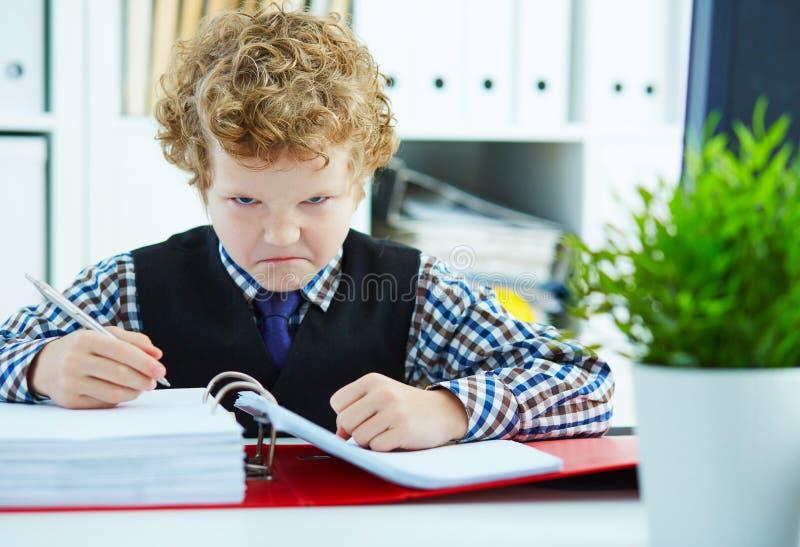 Il piccolo ragazzo riccio arrabbiato gradisce l'uomo d'affari che fa il lavoro di ufficio in ufficio immagini stock