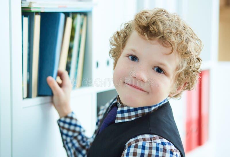 Il piccolo ragazzo riccio caucasico sceglie un libro nella biblioteca immagine stock libera da diritti