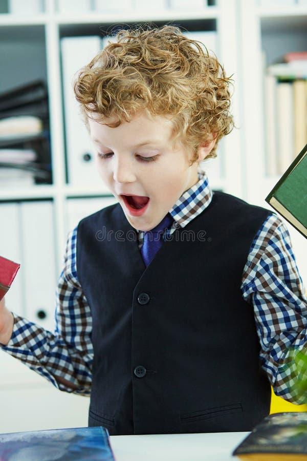 Il piccolo ragazzo riccio caucasico sceglie un libro nella biblioteca fotografia stock libera da diritti