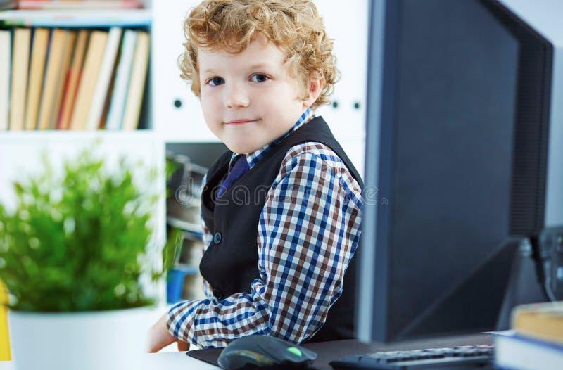Il piccolo ragazzo riccio caucasico si presenta come uomo d'affari che posa vicino al desktop con un monitor nell'ufficio fotografie stock libere da diritti