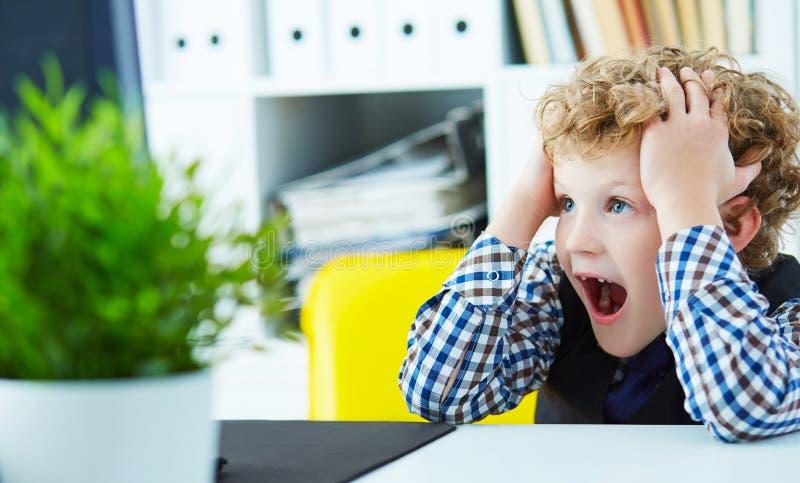Il piccolo ragazzo riccio ha afferrato la sua testa che esamina lo schermo di computer Il concetto di controllo paterno sopra i b immagine stock libera da diritti