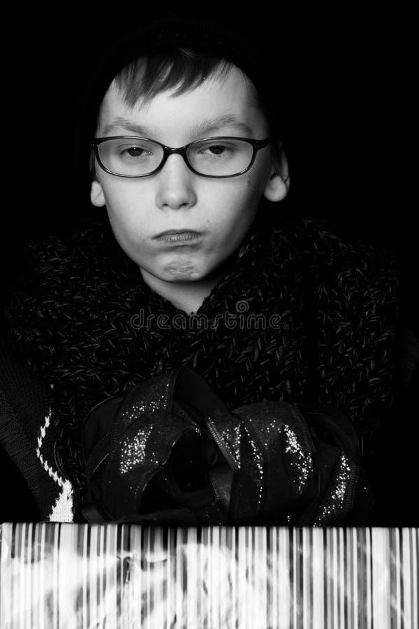 Il piccolo ragazzo serio o il bambino sveglio del nerd in vetri, cappello e sciarpa tricottata alla moda su fondo nero giudica va fotografia stock