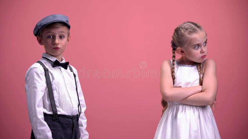 Il piccolo ragazzo sorpreso con le amiche il comportamento, bambini coppia litigare fotografia stock