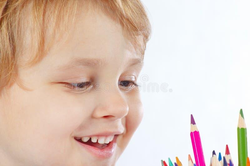 Il piccolo ragazzo sorridente guarda sulle matite di colore fotografie stock