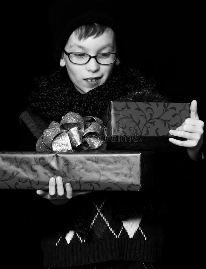 Il piccolo ragazzo sorridente o il bambino sveglio del nerd in vetri, cappello e sciarpa tricottata alla moda su fondo nero giudi fotografia stock