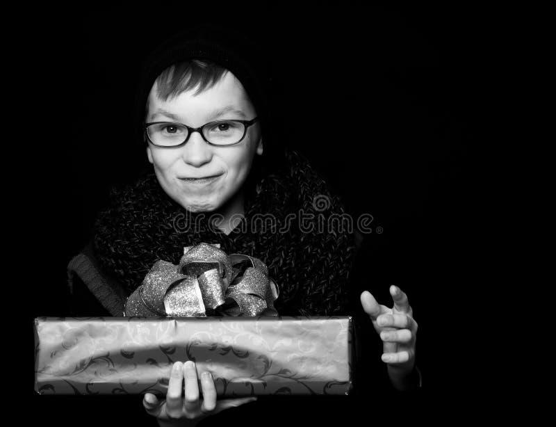 Il piccolo ragazzo sorridente o il bambino sveglio del nerd in vetri, cappello e sciarpa tricottata alla moda su fondo nero giudi fotografie stock