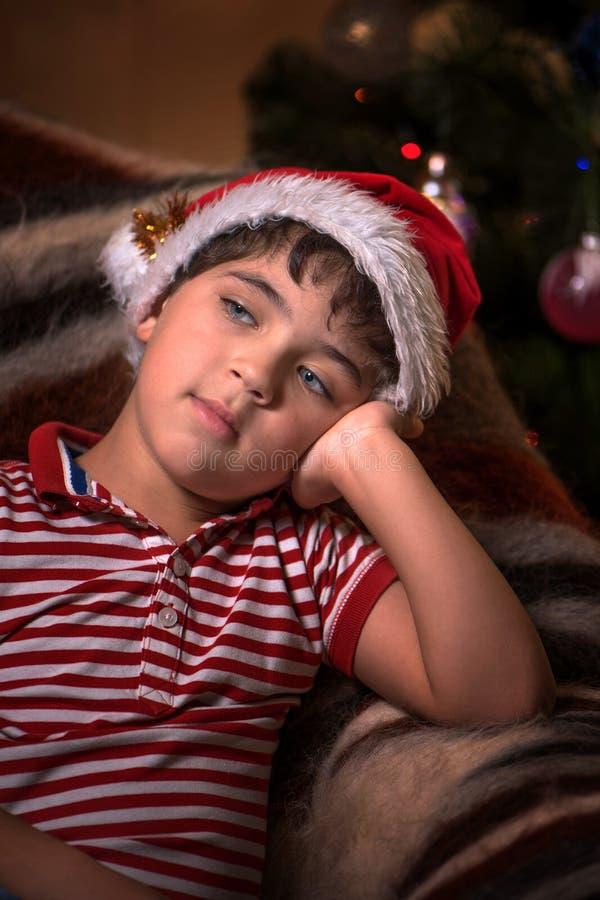 Il piccolo ragazzo sveglio in cappello di Santa sta sognando per un regalo fotografie stock libere da diritti